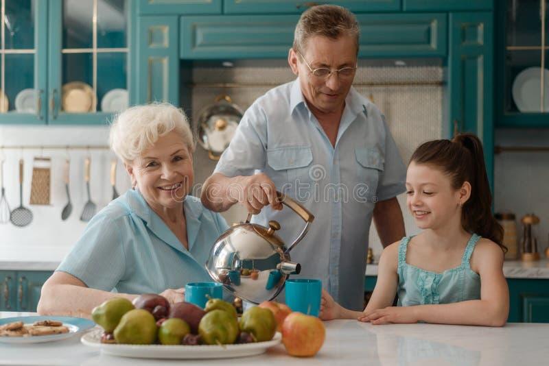 Grandad serving tea for granddaughter royalty free stock image
