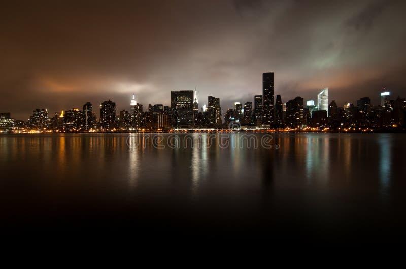 Grandangolare dell'orizzonte di New York alla notte immagine stock