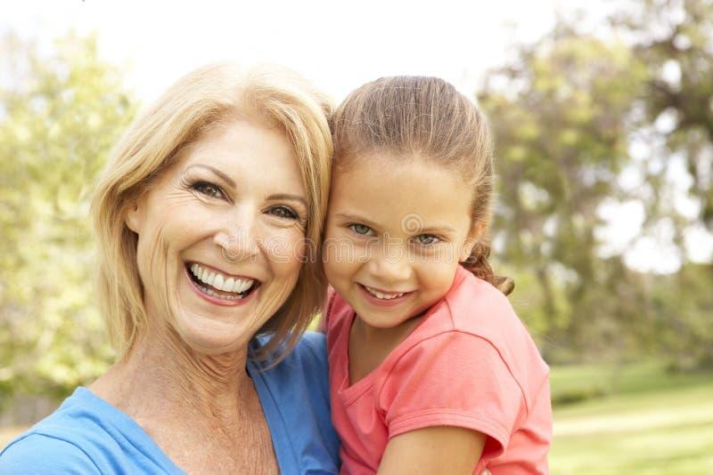 Grandaughter que abraça a avó no parque foto de stock royalty free