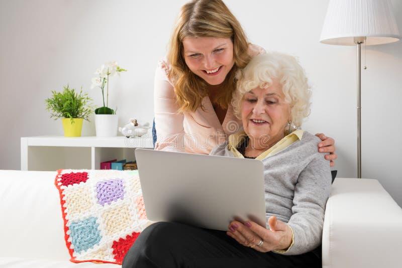 Grandaughter undervisningmormor hur man använder den moderna datoren arkivfoto