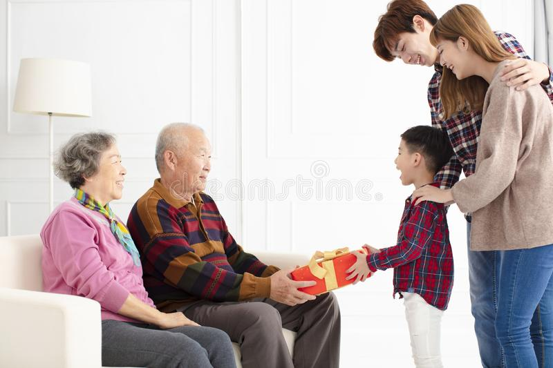 Grandchild with parents giving a gift to grandparents royalty free stock photography
