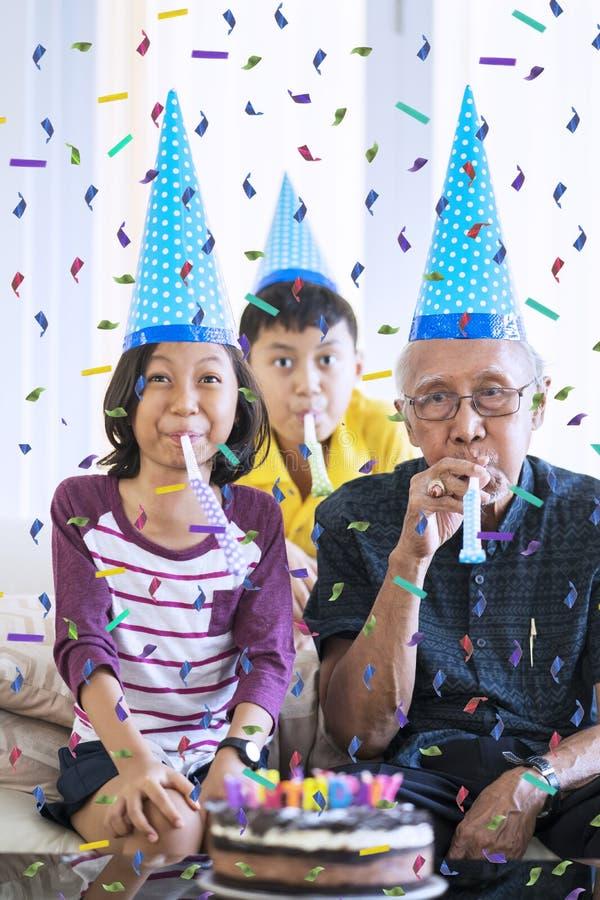 Grandchildren celebrate grandfather birthday royalty free stock photography