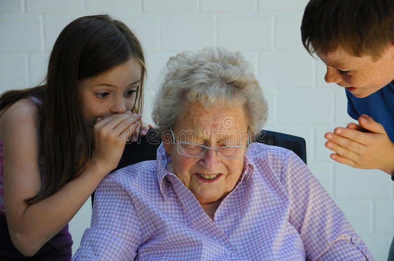 Grandchildren and grandmother. Young and old, grandchildren share a secret with their ninety years old grandmother stock image