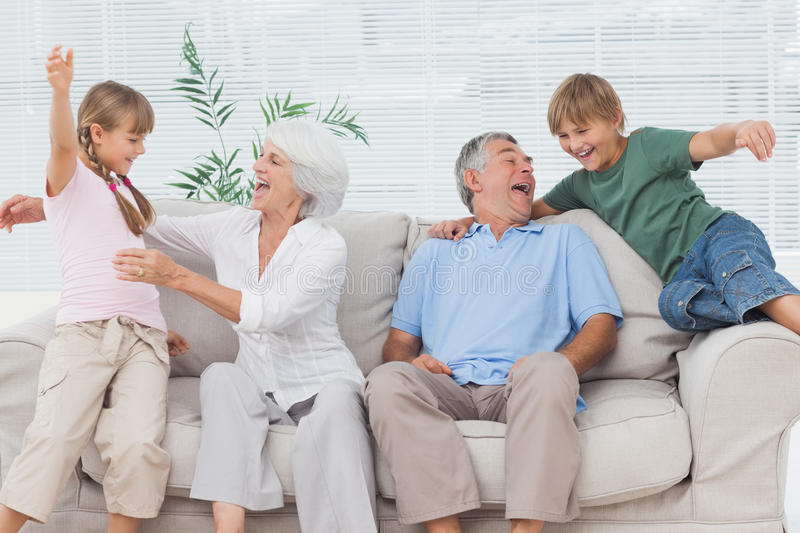 Grandchildren jumping on couch with their grandparents. In the living room royalty free stock image