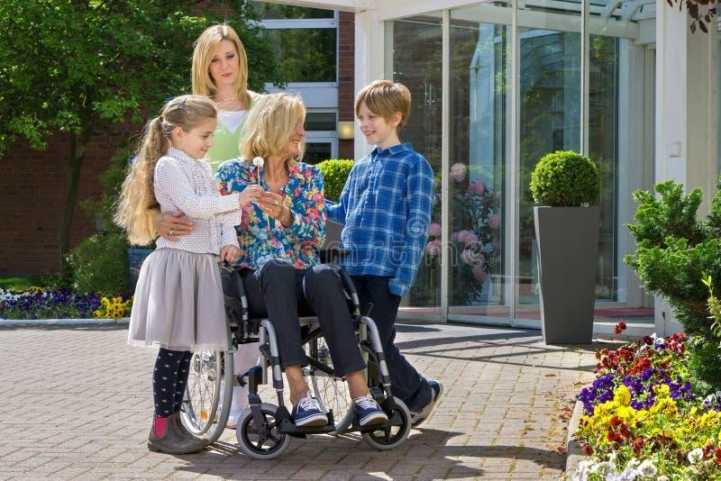 Grandchildren visiting grandmother in wheelchair. Happy cute caring grandchildren with concerned mother visiting youthful looking grandmother in wheelchair stock images