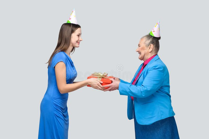 Young woman gives a gift to old funny woman stock photos