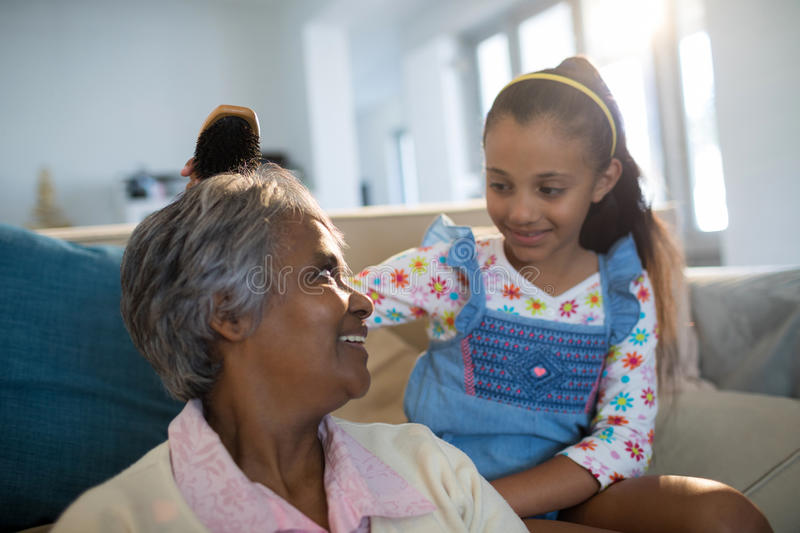 Granddaughter brushing her grandmothers hair in living room. At home royalty free stock image