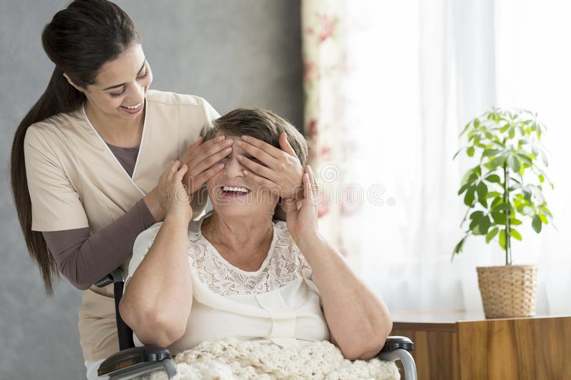 Granddaughter covering grandmother`s eyes stock image