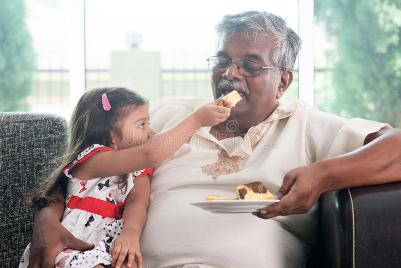 Granddaughter feeding grandfather cake stock images