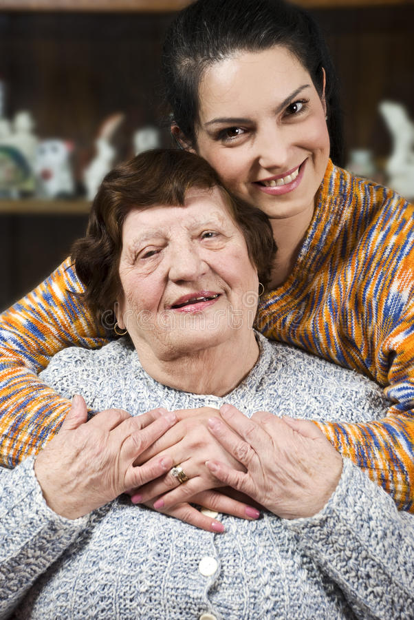 Granddaughter giving a hug to her grandma stock photos