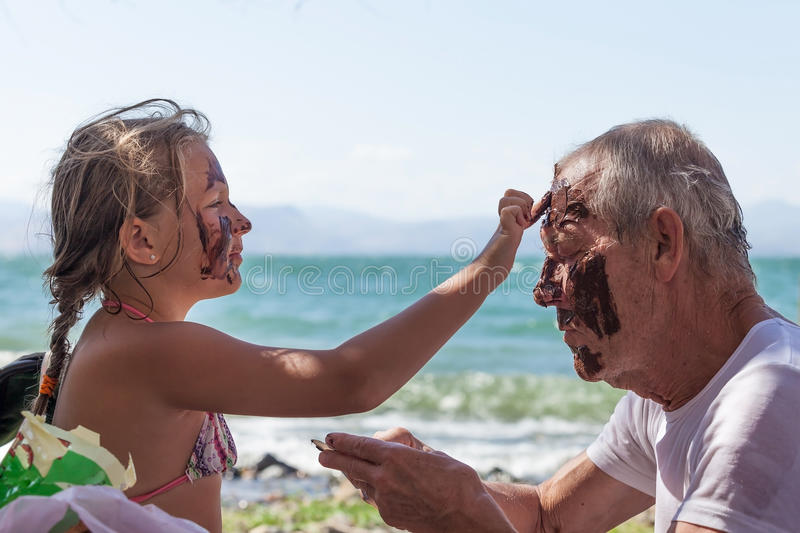 Granddaughter grandfather smears face with mud royalty free stock photography