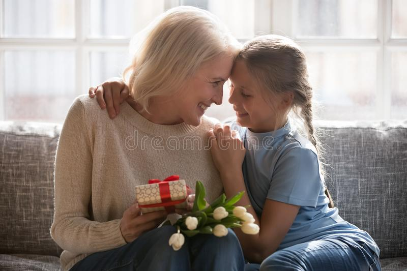Granddaughter grandmother cuddling celebrating granny birthday with flowers and gift stock image
