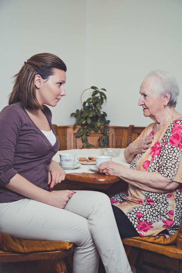 Granddaughter and grandmother talking. Seriously royalty free stock photography