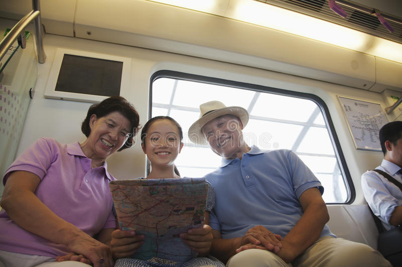 Granddaughter with grandparents sitting in the subway and looking at the map stock images
