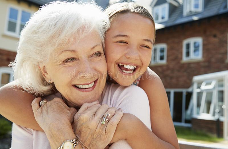 Granddaughter Hugging Grandmother On Bench During Visit To Retirement Home royalty free stock photo