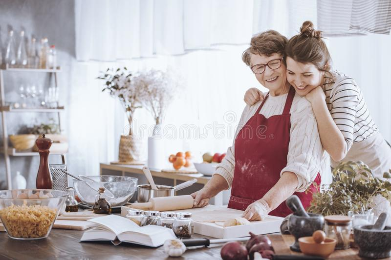 Granddaughter hugging grandmother in the kitchen royalty free stock photography