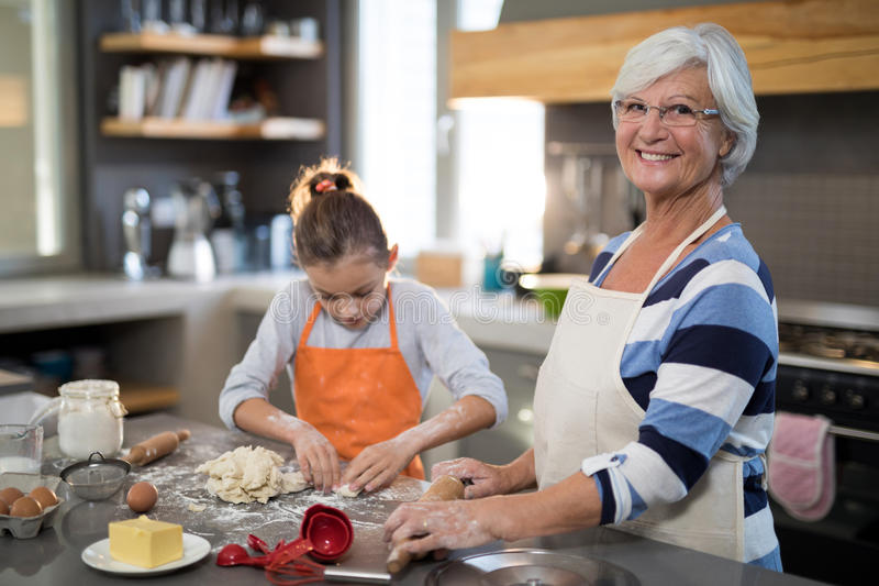 Granddaughter kneading dough royalty free stock photography