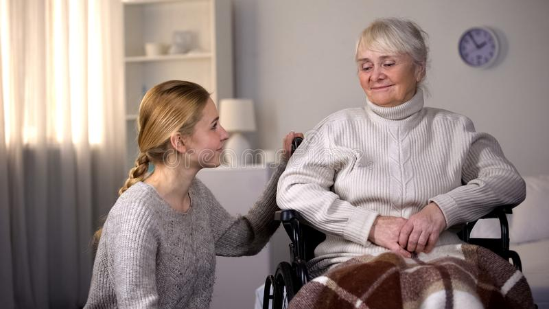 Granddaughter looking at handicapped granny, family care and support, hospital stock image