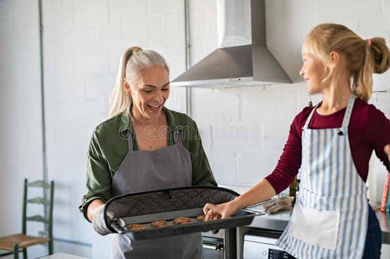 Girl taking hot cookie from bakeware stock images