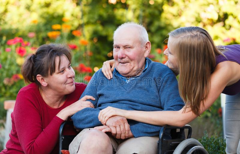 Granddaughter visiting grandpa. The female generation visiting old grandfather at the nursing home royalty free stock photo