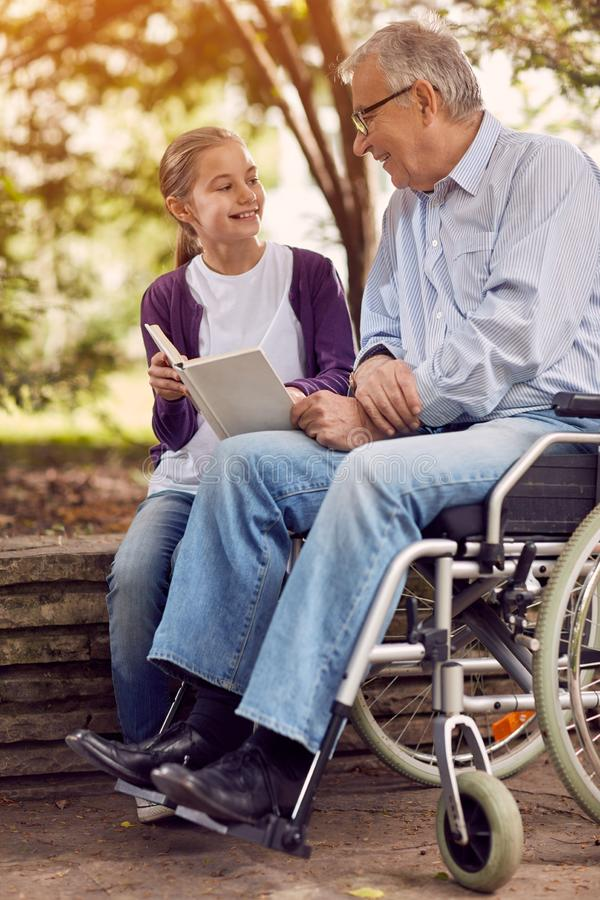 Granddaughter visiting her disabled grandfather in wheelchair an. Young granddaughter visiting her disabled grandfather in wheelchair and enjoying reading book stock photography