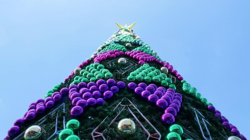 Grande árvore de Natal no céu azul decorado com as bolas brilhantes do verde vívido e do roxo fotos de stock royalty free
