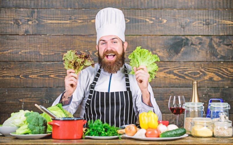 Grande alimento per uno stile di vita sano Uomo barbuto felice ricetta del cuoco unico Alimento biologico stante a dieta Cottura  immagine stock libera da diritti