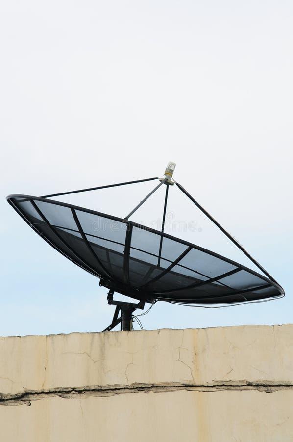 Grande antenne parabolique noire sur l'immeuble de bureaux photo libre de droits
