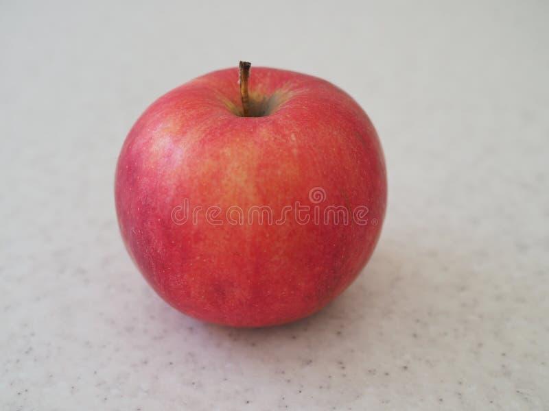 Grande Apple rosso ha isolato sulla tavola di marmo Fine in su fotografia stock