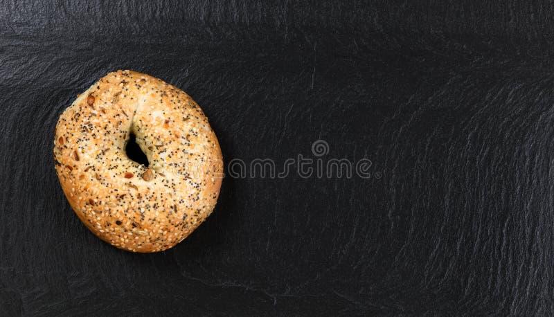 Grande bagel semeado no fundo natural da pedra da ardósia fotos de stock royalty free