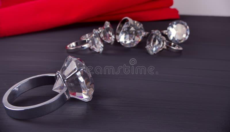 Grande bague à diamant sur la table À l'arrière-plan un groupe d'anneaux et de serviette de table rouge photo stock