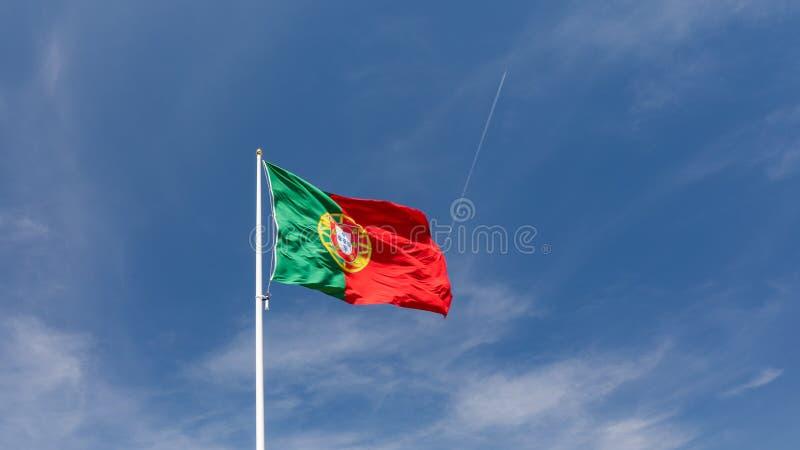 Grande bandeira portuguesa bonita que acena no vento contra o céu azul Bandeira portuguesa que acena contra o c?u azul Bandeira d imagens de stock royalty free