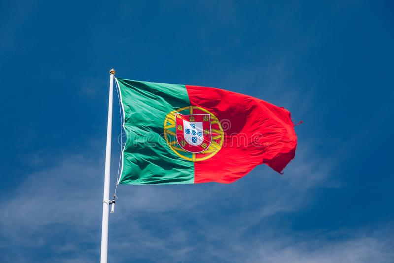 Grande bandeira portuguesa bonita que acena no vento contra o c?u azul Bandeira portuguesa que acena contra o c?u azul Bandeira d imagem de stock royalty free