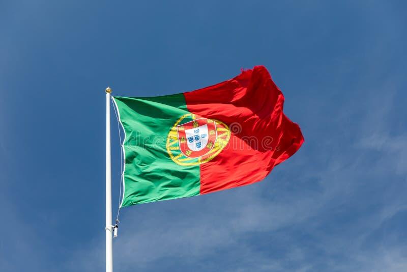 Grande bandeira portuguesa bonita que acena no vento contra o c?u azul Bandeira portuguesa que acena contra o c?u azul Bandeira d foto de stock royalty free