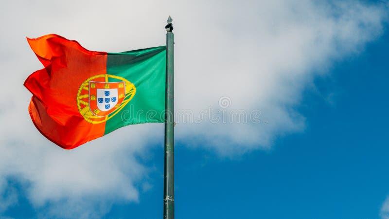 Grande bandeira portuguesa bonita que acena no vento contra um fundo azul em Lisboa, Portugal foto de stock
