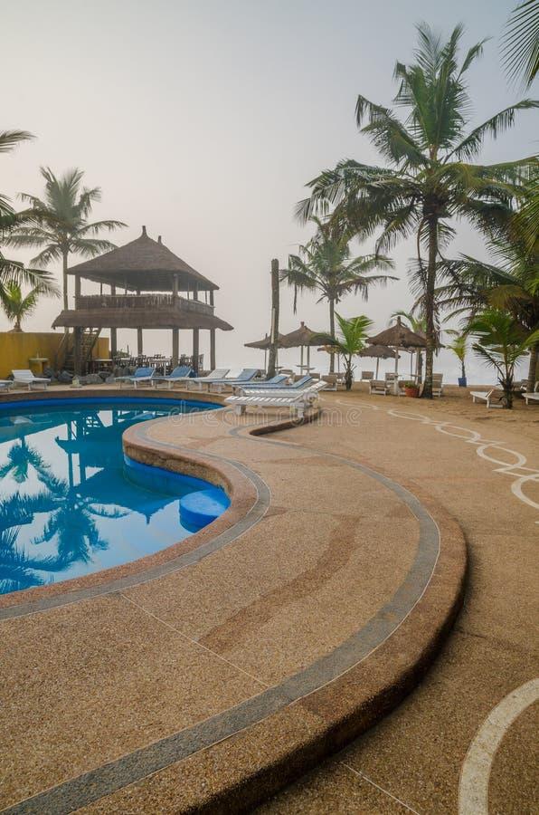 Grande-Bassam, Costa d'Avorio - 2 febbraio 2014: Centro di villeggiatura con lo stagno, le palme ed i ripari ricoperti di paglia  fotografia stock