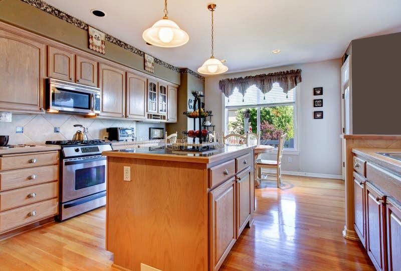 Grande belle cuisine blanche avec le plancher en bois dur et les murs verts. photos stock