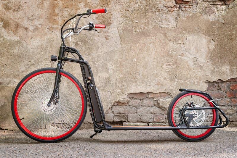 Grande bicicleta elétrica preta do pontapé contra a parede áspera fotos de stock royalty free