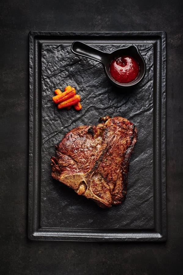 Grande bistecca di bistecca con l'osso del manzo con salsa a fondo di pietra nero immagine stock libera da diritti
