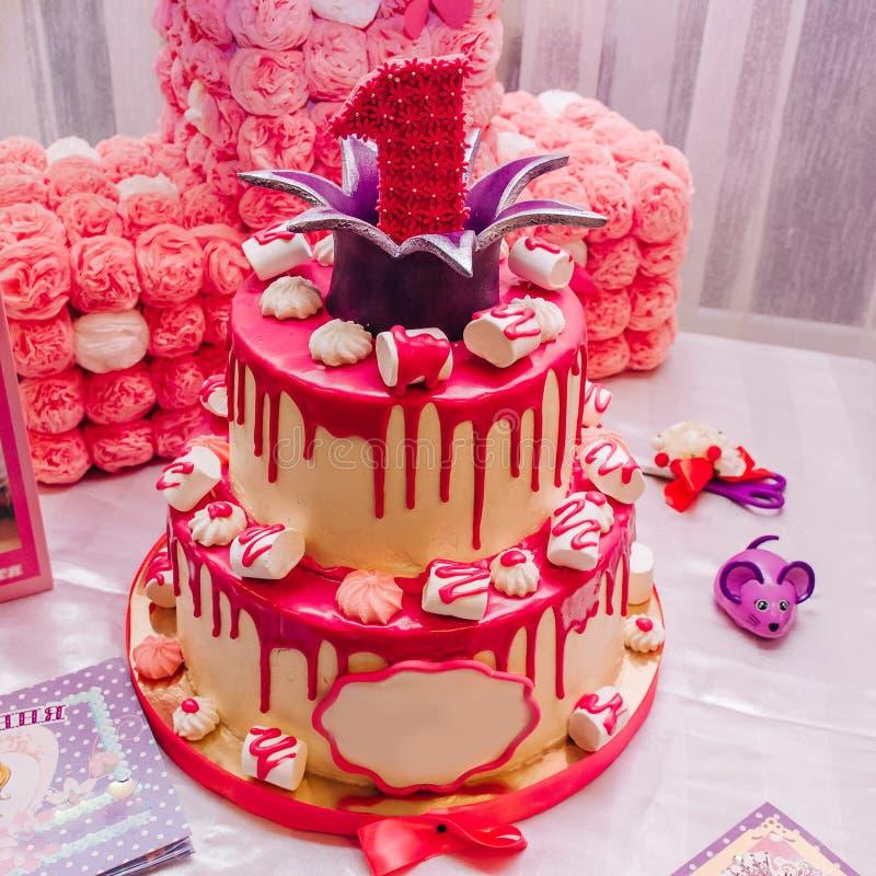 Grande bolo a dois níveis cor-de-rosa com uma unidade na parte superior para um aniversário do ` s das crianças imagem de stock