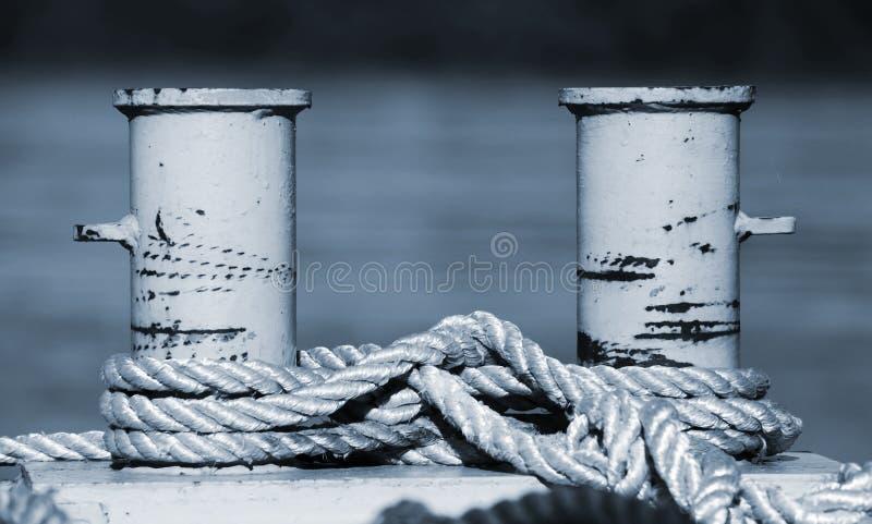 Grande borne d'amarrage avec les cordes nautiques, bleu modifié la tonalité photos stock