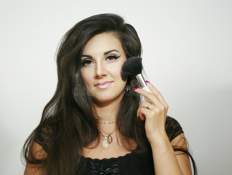 Grande brosse pelucheuse de belle de maquillage utilisation sexy de femme, regards à vous avec le sourire léger image libre de droits