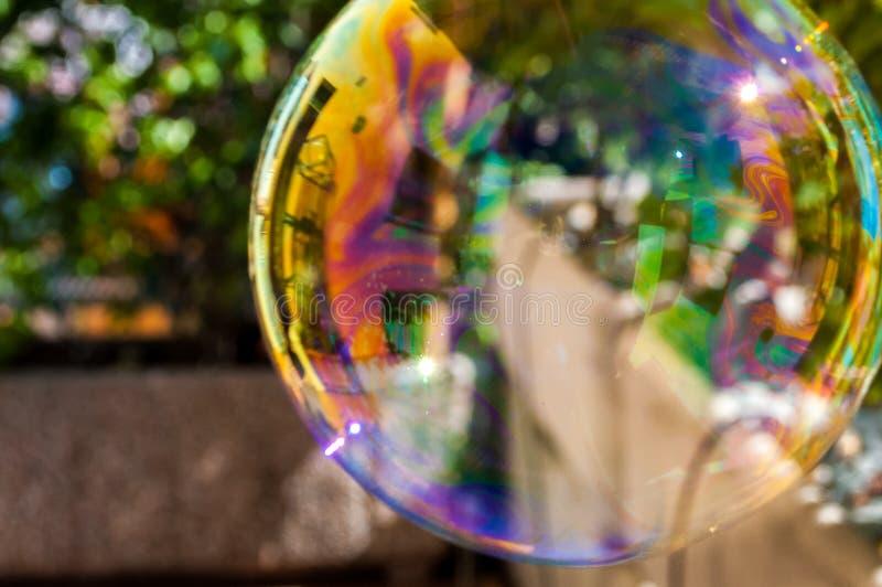 Grande bulle de jeu de savon dans le jardin avec des couleurs d'arc-en-ciel photos libres de droits