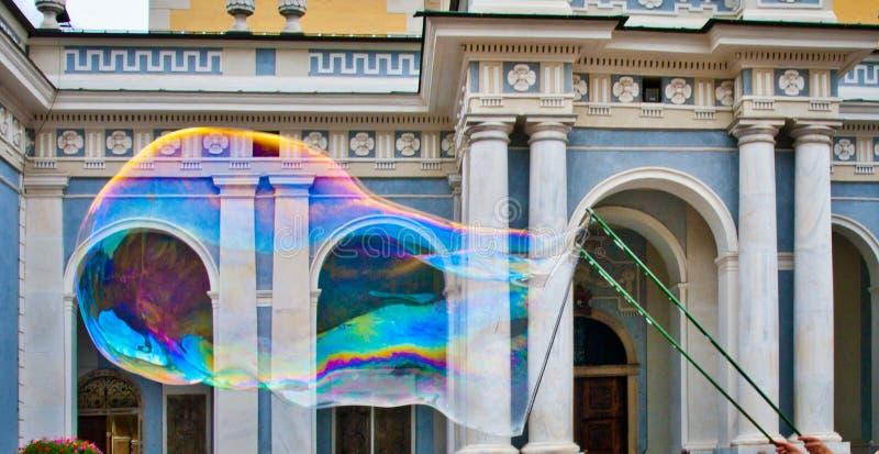 Grande bulle de savon avec mille couleurs devant la cathédrale photographie stock libre de droits