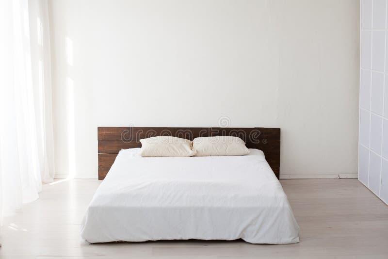 Grande cama nos quartos brancos interiores imagem de stock royalty free