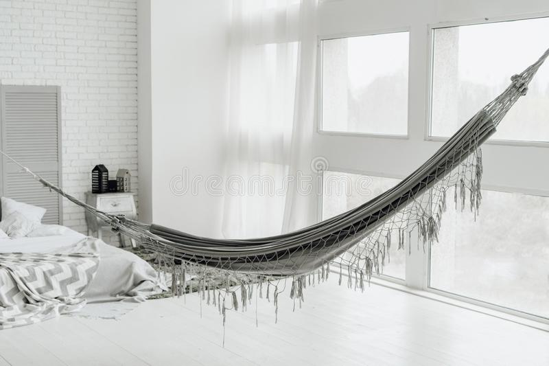 Grande camera da letto accogliente bianca interna con Grey Hammock fotografia stock libera da diritti