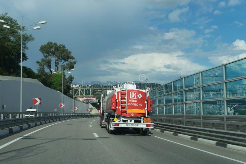 Grande camion cisterna con un carro armato rosso che va sulla strada fotografie stock libere da diritti
