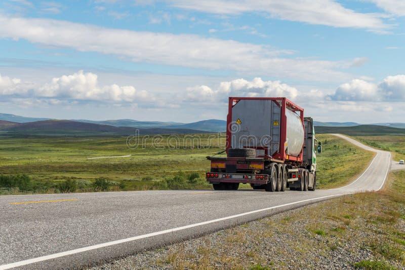 Grande camion cisterna sulla strada su un fondo di un prato verde e delle nuvole immagini stock