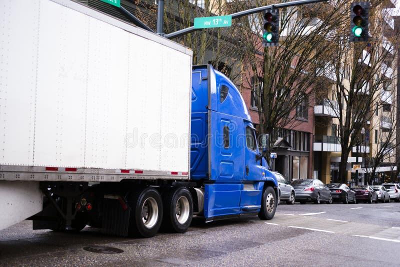 Grande camion dei semi dell'impianto di perforazione in blu con il rimorchio che si muove dallo streptococco urbano della città fotografia stock libera da diritti