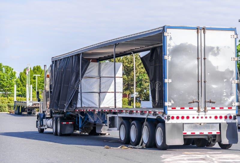Grande camion dei semi dell'impianto di perforazione con il rimorchio coperto aperto dei semi che scarica carico commerciale sul  fotografia stock